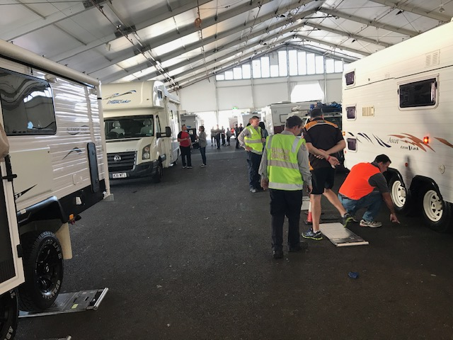 Transport inspectors performing safety inspections on caravans